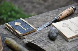 Die Wachstafeln werden aus Holz, Kohlenstaub und Wachs hergestellt. Mit dem Stemmeisen wird die Vertiefung geschaffen.